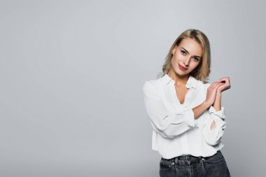 Smiling blonde woman in white shirt looking at camera isolated on grey stock vector