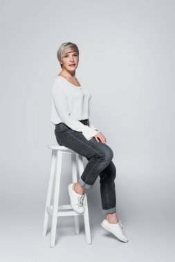 Middle aged woman in jeans and white blouse sitting on high chair on grey stock vector