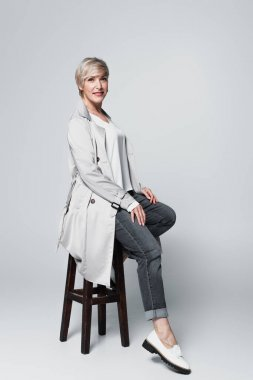 Ash-blonde woman in trendy autumn outfit sitting on high stool on grey stock vector