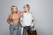 trendy mother and daughter smiling at each other while posing with hands in pockets on grey