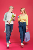 stylish mother and daughter smiling at each other while walking with shopping bags and tulips on pink