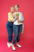 full length view of smiling woman hugging shoulder of joyful mother holding tulips on pink