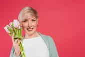stylish woman smiling at camera while holding fresh tulips isolated on pink