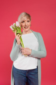 stylish, middle aged woman smiling at camera while holding tulips isolated on pink