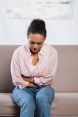 Afričanky americká žena trpí bolestí břicha při sezení na pohovce v obývacím pokoji