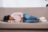 Afrikanerin leidet unter Bauchschmerzen, während sie im Wohnzimmer auf dem Sofa liegt