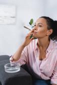 Afrikanische Amerikanerin raucht RollJoint mit medizinischem Cannabis in der Nähe von Aschenbecher
