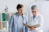 Mature doctor looking at notebook near patient in hospital