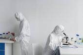 Wissenschaftler in Schutzanzügen arbeiten im Labor an Impfstoffen