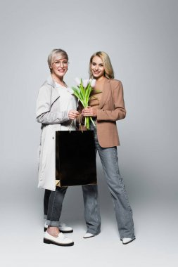 Happy mother and daughter with shopping bag and tulips on grey stock vector