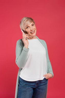 Smiling, ash-blonde woman talking on mobile phone while holding hand in pocket isolated on pink stock vector