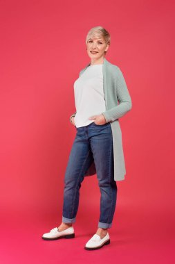 Full length view of trendy woman posing with hands in pockets of jeans on pink stock vector
