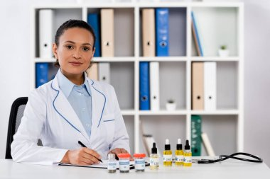 African american doctor writing prescription on clipboard near bottles with legal cbd and medical cannabis stock vector