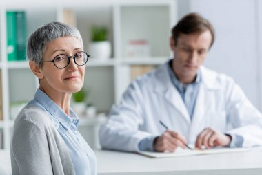 Mature patient looking at camera near doctor on blurred background stock vector