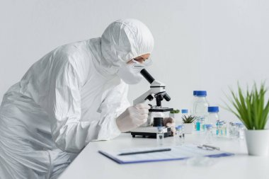 Scientist in protective uniform using microscope near vaccines and clipboard on blurred foreground stock vector