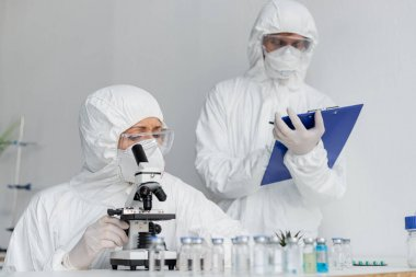 Scientist in protective uniform using microscope near colleague and vaccines on blurred foreground stock vector
