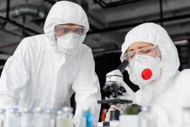 Scientist standing near colleague using microscope and vaccines on blurred foreground stock vector