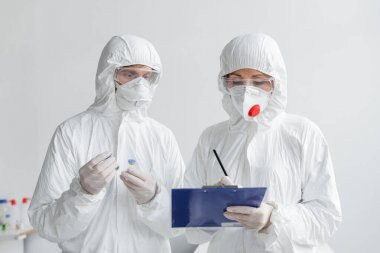 Scientists in hazmat suits working with vaccines and clipboard in laboratory stock vector