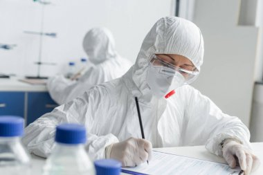 Scientist writing on clipboard near colleague on blurred background in laboratory stock vector