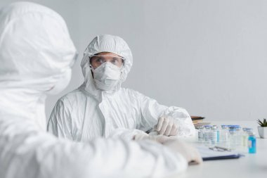 Scientist in hazmat suit looking at colleague near clipboard and vaccines stock vector