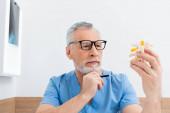 rehabilitolog v brýlích držící pero při pohledu na model páteře