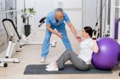 středního věku rehabilitolog mluví se ženou sedí na fitness muže v nemocniční tělocvičně