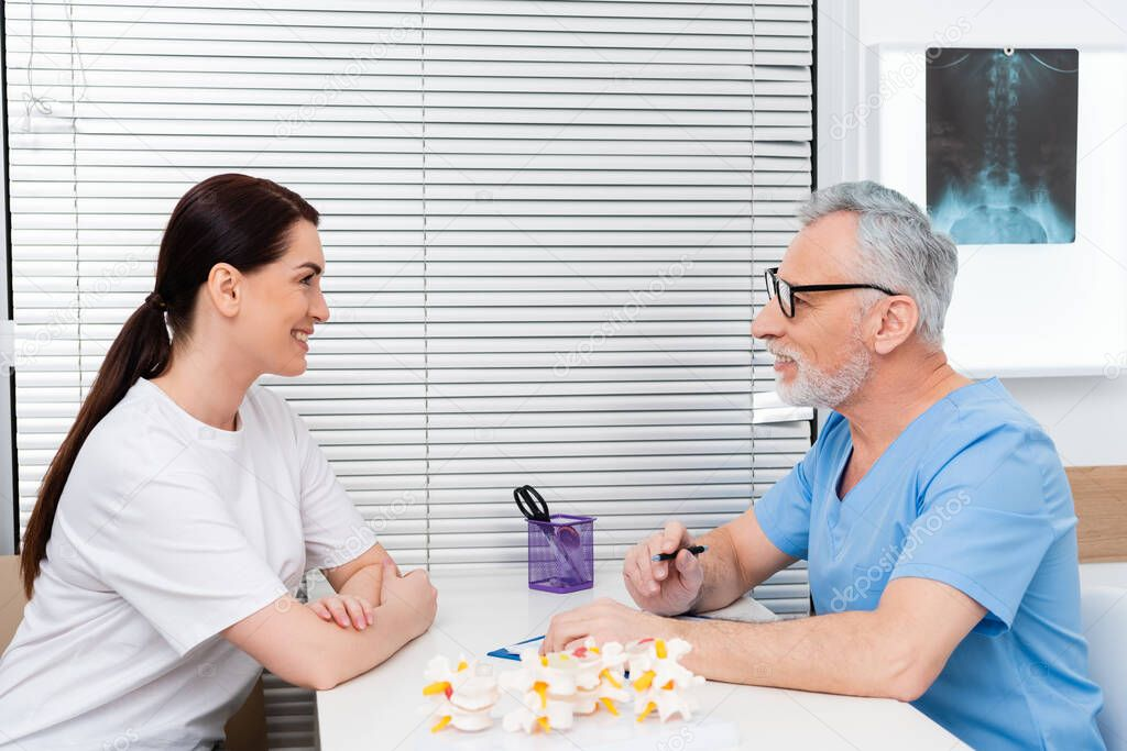 Middle aged rehabilitologist talking to smiling woman near spine model on desk stock vector