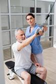 brunetka fyzioterapeut pomáhá dospělé muže školení v rehabilitační centrum