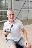 usmívající se muž školení na tahání lano cvičení stroj v nemocniční tělocvičně