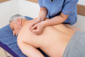masérka dělá masáž zad pro dospělého muže ležícího na masážním stole