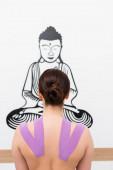 zadní pohled brunetky ženy při kinezioterapii v blízkosti buddhovy kresby na stěně