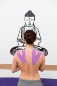 pohled na ženu stojící před buddou kreslící na stěně při kinezioterapii