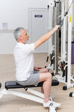 Side view of mature man working out on exercising machine during rehabilitation stock vector