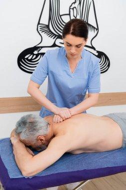 Brunette masseuse doing back massage to mature man stock vector