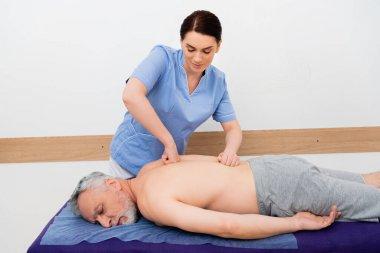 Pretty, brunette masseuse doing back massage to mature man in hospital stock vector