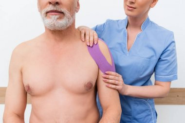 Cropped view of rehabilitologist applying kinesio tape on shoulder of mature man stock vector