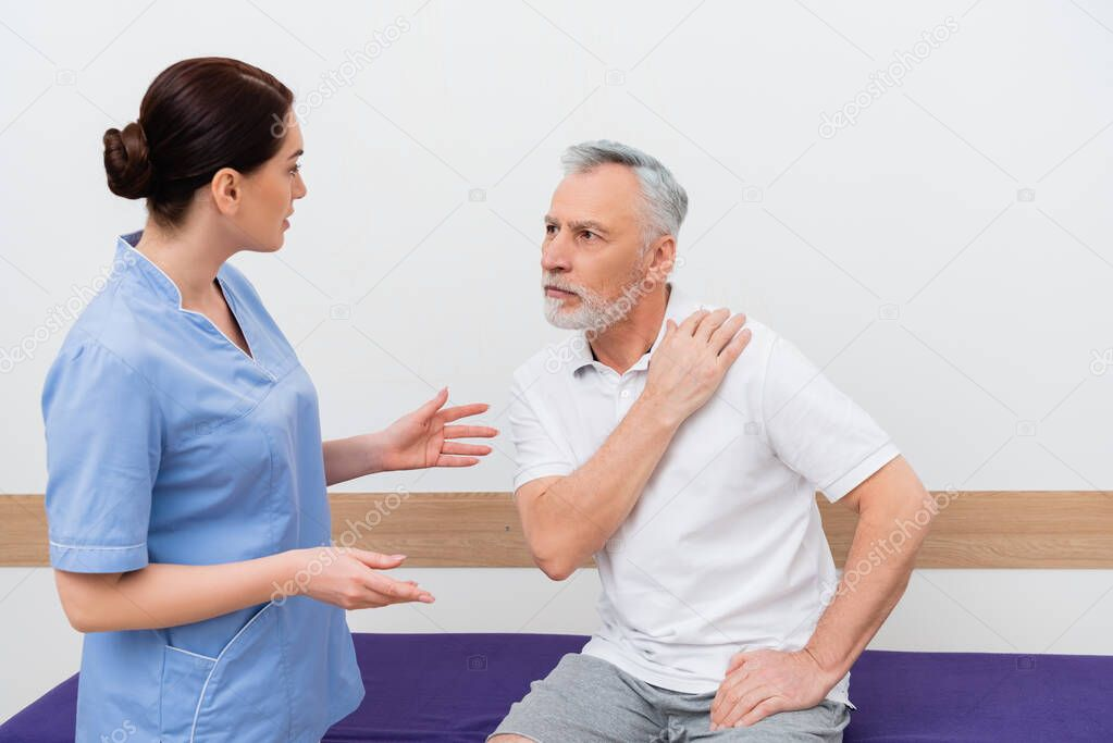 Rehabilitologist gesturing while talking to mature man touching shoulder in clinic stock vector