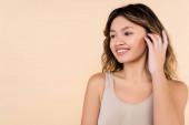 mladá asijská žena opravuje vlasy a usmívá izolované na béžové