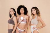 různé ženy ve spodním prádle při pohledu na kameru v blízkosti africké americké ženy s kosmetickou smetanou izolované na béžové