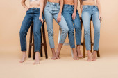 partial view of barefoot women in jeans posing near high stools on beige