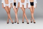částečný pohled na štíhlé ženy v košilích, kalhotkách a obuvi stojící na šedé