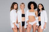 sexy multikulturní ženy ve spodním prádle a bílé košile při pohledu na kameru izolované na šedé