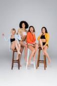 vzrušené mezirasové ženy ve spodním prádle a košile pózují na vysokých stoličkách na šedé