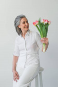 Smiling grey haired woman looking at bouquet of tulips isolated on grey