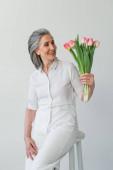 Usmívající se šedovlasá žena se dívá na kytici tulipánů izolovaných na šedi