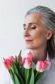 Portrét dospělé ženy držící tulipány izolované na šedi