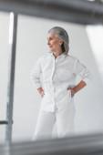 Lächelnde Frau mittleren Alters mit Händen auf Hüften in der Nähe von Metallrohren auf grauem Hintergrund