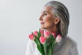 Starší žena s růžovými tulipány odvrací izolované na šedé