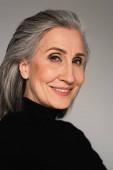 Portrét usměvavé dospělé ženy izolované na šedé