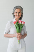Pozitív érett nő fehér ing gazdaság tulipán elszigetelt szürke
